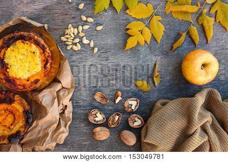 Millet porridge baked in pumpkin, walnut, seeds, apple, yellow leaves, warm sweater on an old wooden background.