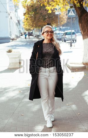 Blond woman wearing black coat, white pants, hipster glasses walking on the sidewalk on city street in autumn. Fall casual fashion, elegant everyday look. Plus size model.