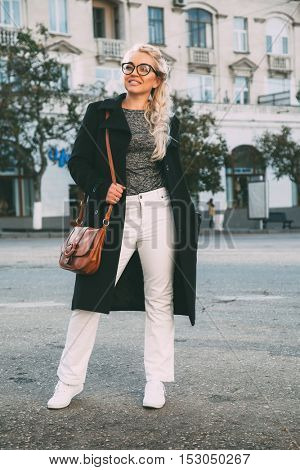 Blond woman wearing black midi coat, white pants, hipster glasses and holding brown leather handbag walking on the city street in autumn. Fall casual fashion, elegant everyday look. Plus size model.