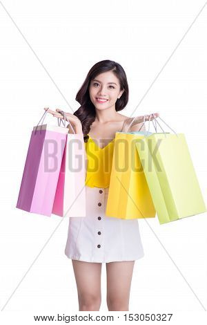Asian smiling young woman holding colorful paper bags. Concept for shop sales. Isolated on white background