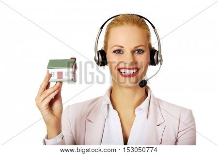 Young business woman in headset holding house model