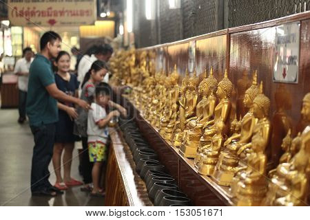 Chachoengsao,Thailand-October 15,Family pay coins in 109 monk bowls next Buddha images in Buddhist worship way at Wat Sothon Wararam Worawihan on October 15,2016 ,Thailand. Selective focus.