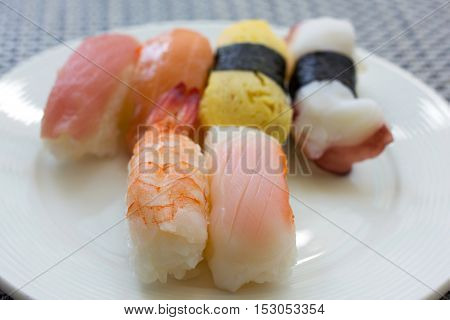 Japanese sushi on a white plate with selective focus and low contrast