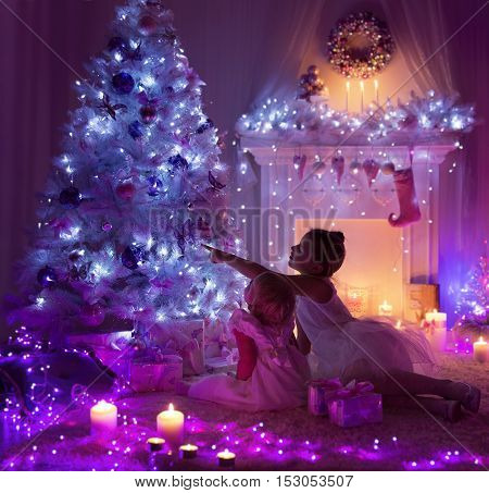 Kids Celebrating Christmas Child and Baby Decorated Xmas Tree Fire Place Lights in Night Room Interior