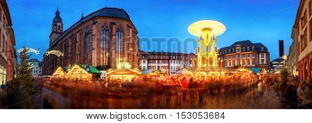 Christmas market in Heidelberg Germany a panorama shot at dusk showing illuminated kiosks historic architecture and blurred people