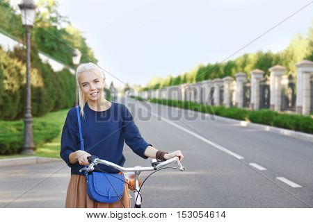 Young woman with bicycle in park on blurred background