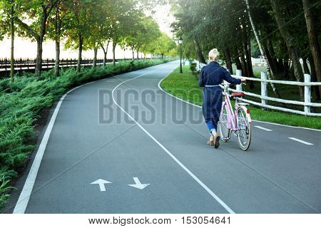 Young woman with bicycle walking along bikeway in green park