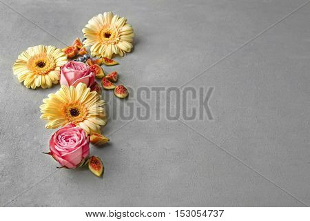 Composition of roses, daisy flowers and figs on light textured background