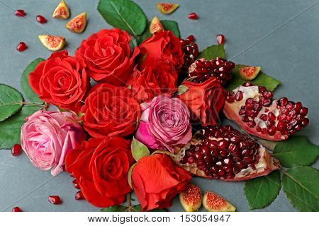 Composition of roses, pomegranate pieces and figs on color background
