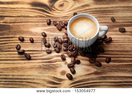 Roasted coffee beans with cup on wooden background