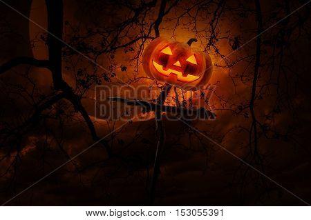 Jack O Lantern pumpkin on wood cross over dead tree moon and cloudy sky Halloween concept