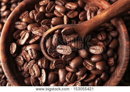 Wooden bowl with coffee beans and spoon, close up view