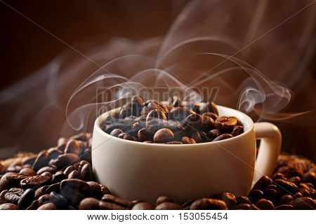 White cup and coffee beans on dark background, close up view