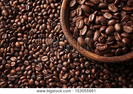 Wooden bowl with coffee beans, close up view
