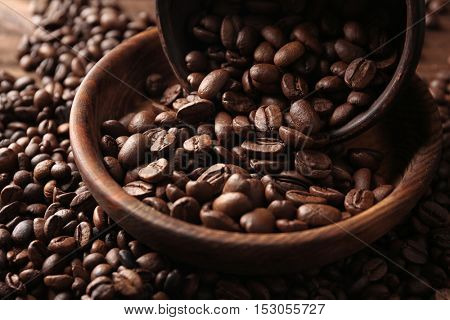 Bowls with coffee beans on wooden background, close up view