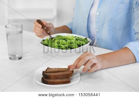 Woman eating fresh delicious salad at table