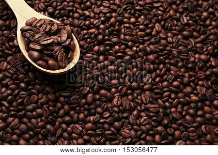 Wooden spoon with roasted coffee beans