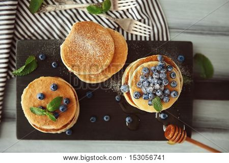 Delicious pancakes with blueberries, honey and mint on wooden cutting board