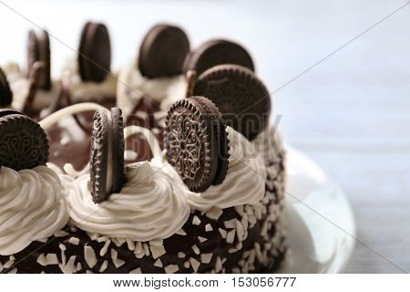 Tasty cake with chocolate cookies and cream on blurred background, close up view