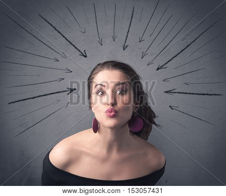 A teenage student girl under pressure while making happy face expressions illustrated with black arrows pointing at her head on the wall blackground concept.