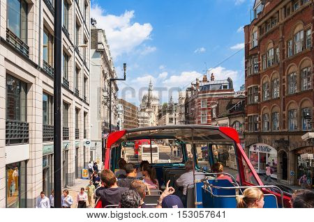 London UK - June 08 2006: Tourists on open-top double-decker sightseeing tour bus in Fleet street in the City of London. Bus with audio guide is the great way see the London's major sights in short time.