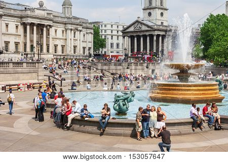 London UK - June 08 2006: Tourists visit Trafalgar Square in front of the National Gallery and the Church of Saint Martin in the Fields on a sunny day. It is one of the most popular tourist attraction in London often considered the heart of London.