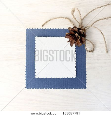 flat lay with the forest cone and clean card for inscriptions on a light wood surface top view / background for congratulation with winter holidays