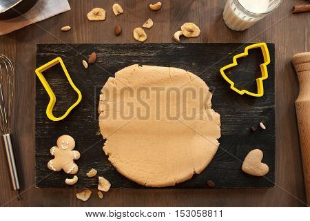Gingerbread dough with cookies and culinary forms of Santa boot and Christmas tree on kitchen table. Homemade pastry, xmas spirit, winter holidays concept