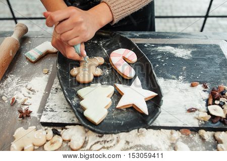 Gingerbread cookies decorating with cream. Christmas traditional treat icing. Homemade bakery, xmas sweet, winter holidays concept