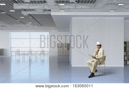 Businessman reading on tablet pc . Mixed media