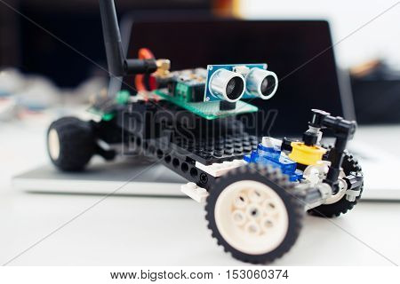 Close-up of little handmade toy car. Children auto made from construction and electronic components. Hobby, leisure, diy, robotics concept