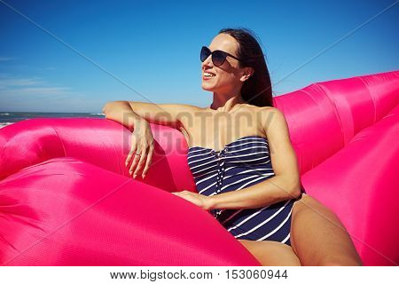 A lovely woman sitting on a pink inflatable boat on the beach. A woman wearing sunglasses and her hair loose looking at the horizon and smiling in stripes swimsuit. Gorgeous weather and cloudless sky