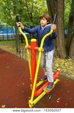 preteen boy exercising on outdoor public free elliptical trainer on autumn street background