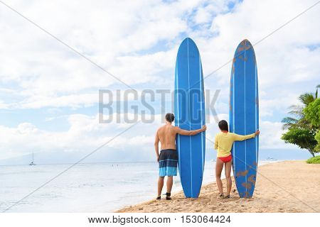 Two people young couple surfers standing with long blue surfboards on hawaii Kaanapali beach after surf class. Fun surfing sport activity on Maui touristic beach for summer vacations.