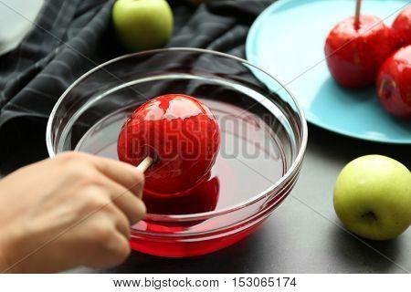 Female hand making caramel apples
