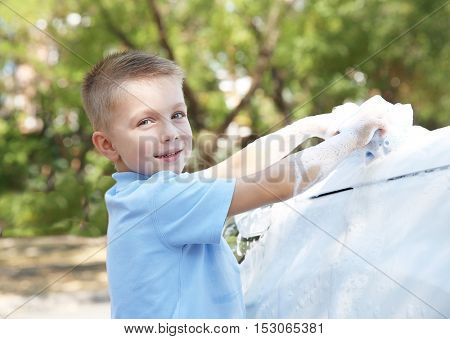 Small boy washing car with sponge on street