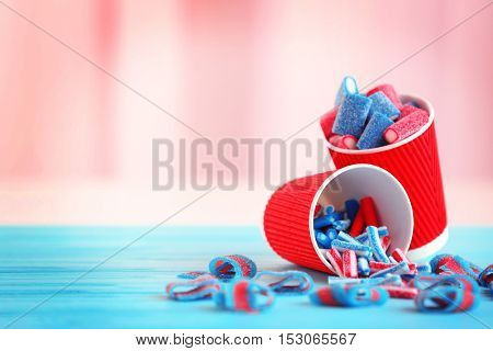 Delicious candies in paper cup on blue wooden table