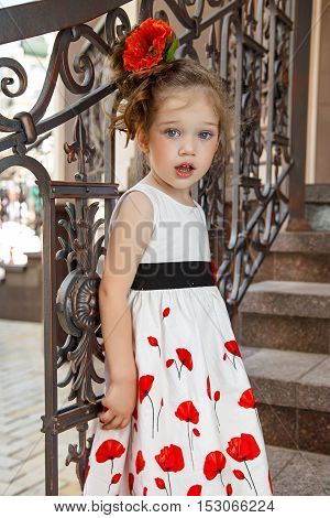 beautiful little girl with a flower in her hair standing near a wrought fence. girl in white dress.