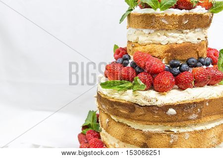 wedding cake with open biscuit shortcakes cream and fruit. blueberries strawberries raspberries red currants.