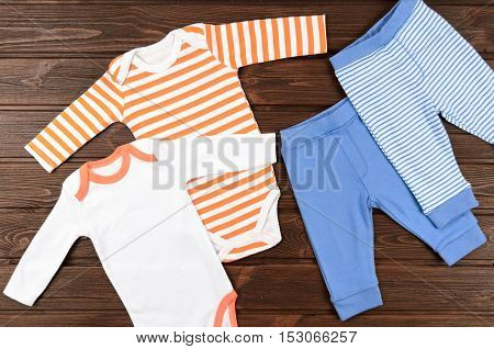 Two Babies Bodysuits And Pants On Wooden Background. Baby Clothes