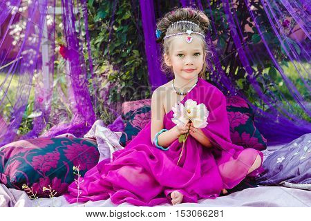 small European girl in oriental dress crimson color in a tent outdoors harmony staged shooting