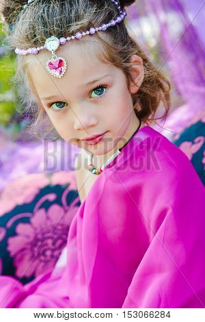 small European girl in oriental dress crimson color with rose in a tent outdoors harmony staged shooting