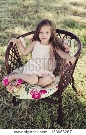 beautiful little girl with flowing hair sitting in a wicker chair. a girl wearing a pink dress. in the background is the field