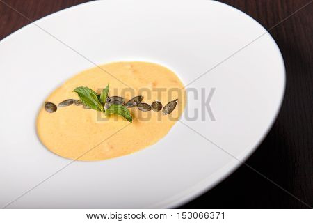 pumpkin cream soup in a white plate on a dark wooden table. on a soup are beans pumpkin and basil leaves. top view