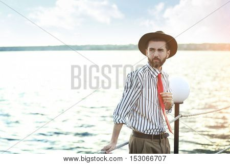 Man in striped shirt and red leather tie on a pier