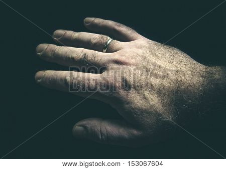 Low key monochrome photos. Man's hand, an engagement ring on her finger. Close-up.