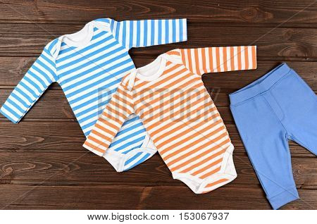 Babies Bodysuits And Pants On Wooden Background. Baby Clothes