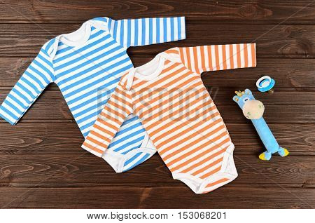 Babies Striped Bodysuits, Toy And Pacifier On Wooden Background. Baby Clothes
