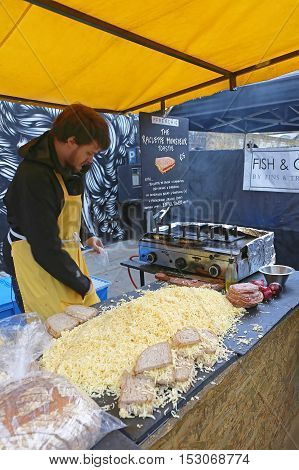 LONDON UNITED KINGDOM - NOVEMBER 24: Grilled Cheese Sandwich Vendor in London on NOVEMBER 24 2013. French Raclette Cheese Toast at Brick Lane Stall in London United Kingdom.
