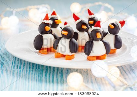 olive penguins snack with mozzarella, carrot and pepper santa hat